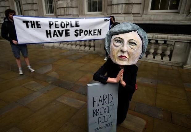 Manifestante usa máscara de primeira-ministra britânica, Theresa May, um dia após eleição no Reino Unido em que o Partido Conservador perdeu maioria no Parlamento (Foto: Clodagh Kilcoyne/Reuters)