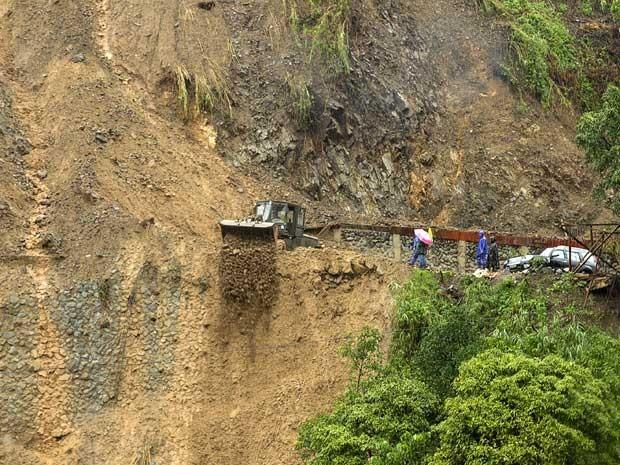 Operários trabalham para desobstruir estrada fechada após deslizamento de terra nas Filipinas (Foto: Harley Palangchao / Reuters)