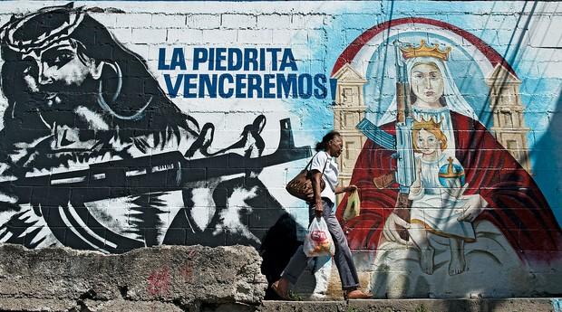 JESUS EM ARMAS Um grafite na Venezuela mostra Jesus com um fuzil.  Ele virou símbolo revolucionário (Foto: Miguel Gutierrez/AFP)