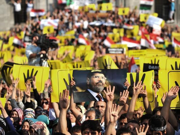 Manifestantes seguram cartazes durante uma manifestação condenando a recente repressão militar aos apoiadores de Morsi no Cairo, em Istambul. (Foto: Ozan Kose/AFP)