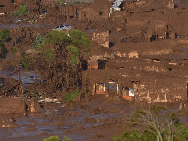 06/11 - Carros e casas são vistos em meio a lama após o rompimento de uma barragem de rejeitos da mineradora Samarco no Distrito de Bento Rodrigues, no interior de Minas Gerais (Foto: Douglas Magno/AFP)