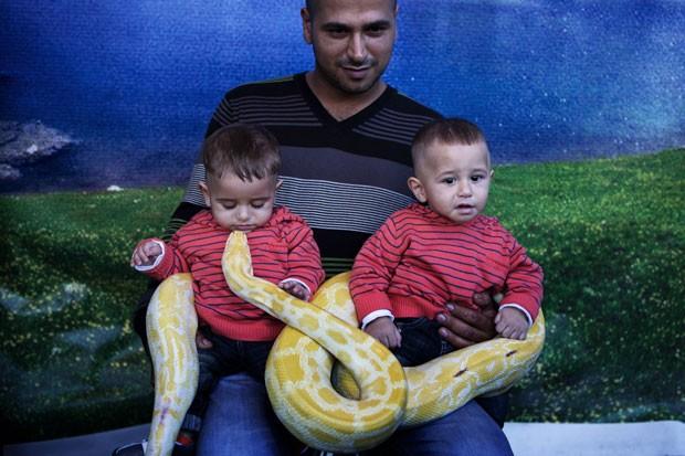 Um pai posou com seus dois filhos enrolados com uma píton albina na cidade de Acre, em Israel, no sábado (27). As crianças pareciam não estar assustadas com o réptil. (Foto: Menahem Kahana/AFP)
