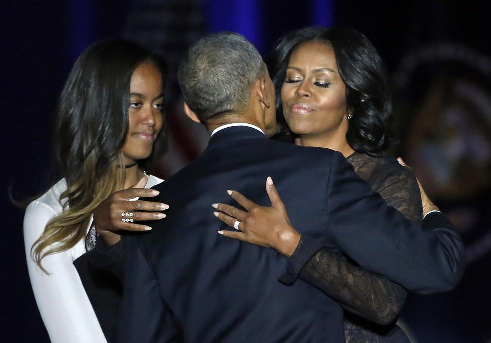 Barack Obama é abraçado por sua mulher, Michelle, e observado pela filha mais velha, Malia (Foto: Charles Rex Arbogast/AP)
