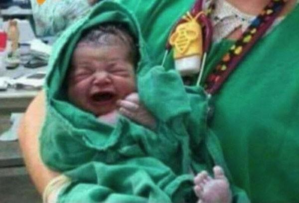 Foto de recém-nascido nos braços da enfermeira (Foto: Divulgação)