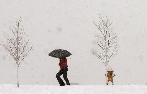 Pessoa com guarda-chuva tenta se proteger de tempestade de neve em Lawrence, no Kansas (Foto: Orlin Wagner/AP)