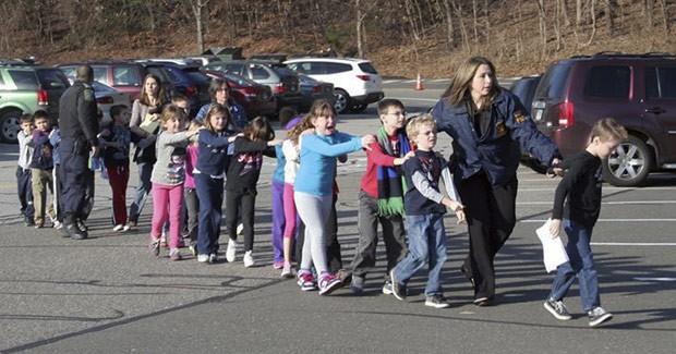 Foto de jornal local mostra crianças sendo retiradas da escola em Newtown, Connecticuc, em que ocorreu o tiroteio nesta sexta-feira (14) (Foto: AP)
