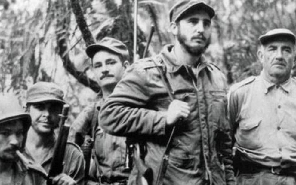 1957 - Armado, Fidel (ao centro, em pé) é visto com companheiros da guerrilha que lutou pelo poder de Cuba, entre eles o irmão Raúl Castro (baixo) e Che Guevara (segundo da esquerda para a direita) (Foto: AFP)