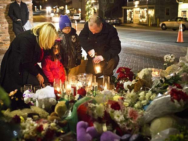 Muito moradores, como o casal Steven e Norma Macchia, e seus filhos de 7 e 3 anos, acenderam velas e rezaram na noite deste sábado (22) em um memorial para as vítimas do massacre. (Foto: Andrew Burton / Reuters)
