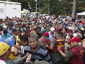 Soldados venezuelanos tentam controlar a multidão que quer comprar frangos no mercado estatal Mega-Mercal neste sábado (24) (Foto: Reuters/Carlos Garcia Rawlins )