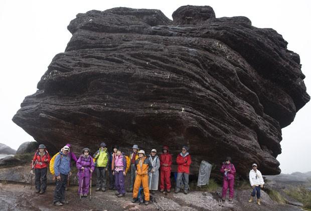Turistas japoneses se abrigam da chuva em uma formação rochosa no Monte Roraima (Foto: Carlos Garcia Rawlins/Reuters)