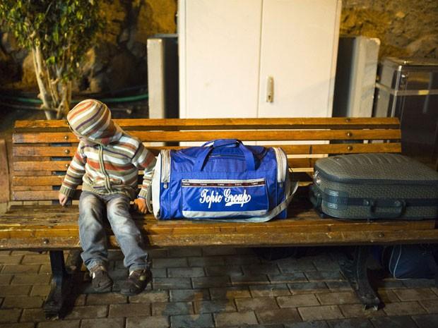 Menino espera na fronteira entre Israel e Sinai, no Egito, perto do Mar Vermelho,no resort de Eilat, para embarcar com sua família para o Egito neste domingo (16) (Foto: Amir Cohen/Reuters)