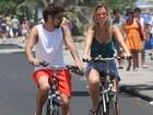 De shortinho, Juliana Didone pedala na orla da praia com o namorado