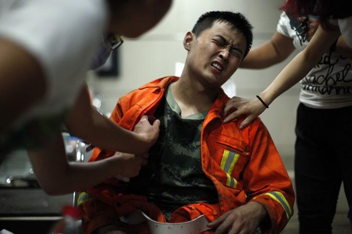 Bombeiro faz cara de dor ao ser examinado após trabalhar no local da explosão em Tianjin (Foto: AP)