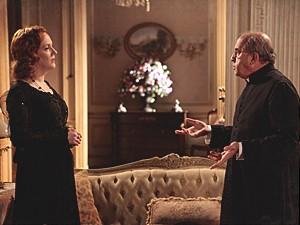 Carlota encontra o padre na sala de sua casa (Foto: Lado a Lado / TV Globo)