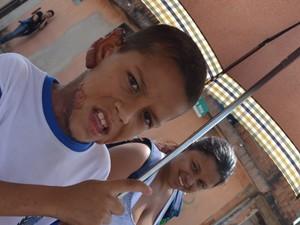 Gustavo vai para a escola na companhia da mãe e sob guarda-chuva para evitar o sol (Foto: Fábio de Souza/Arquivo pessoal)