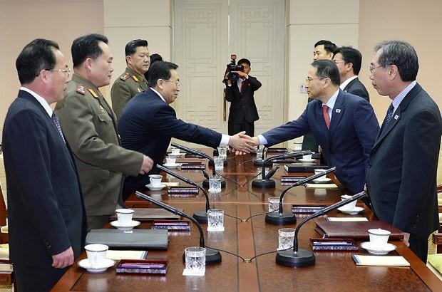 Delegações da Coreia do Norte (à esquerda) e da Coreia do Sul durante encontro nesta quarta-feira (12) na cidade sul-coreana de Panumjom (Foto: AP)