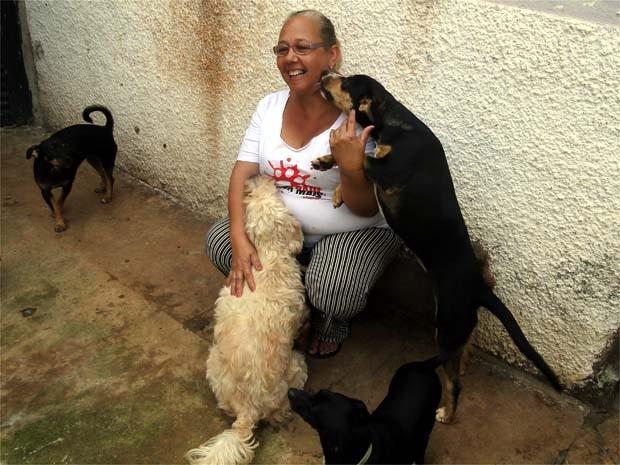 A tosadora recebe o carinho da cadela Fênix, que foi resgatada no meio do lixo e estava doente (Foto: Eduardo Guidini/ G1)