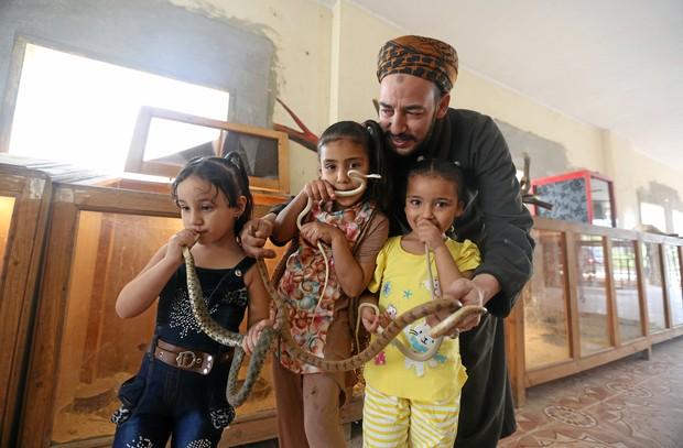 Salah Tolba ensinou suas três filhas a manipularem cobras (Foto: Mohamed Abd El Ghany/Reuters)
