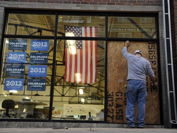 Trabalhador coloca um tapume no lugar da vidraça estilhaçada por um disparo ao escritório de um comitê de Obama (Foto: The Denver Post, Daniel Petty/AP Photo)