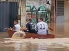 Moradores usam barcos para sair de casas alagadas após temporal