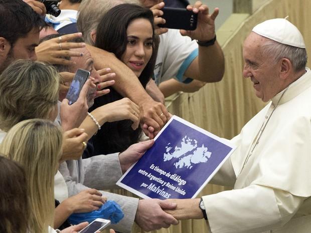 Fiel entrega ao Papa Francisco um cartaz com a mensagem 'É tempo de diálogo entre Argentina e Reino Unido pelas Malvinas', durante audiência semanal na sala Paulo VI, no Vaticano, na quarta (19) (Foto: Claudio Peri/ANSA Via AP)