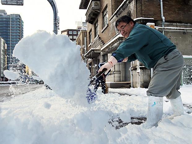 Homem remove neve em calçada de Nagoya, em Aichi, no centro do Japão nesta quinta-feira (18) (Foto: Jiji Press/AFP)