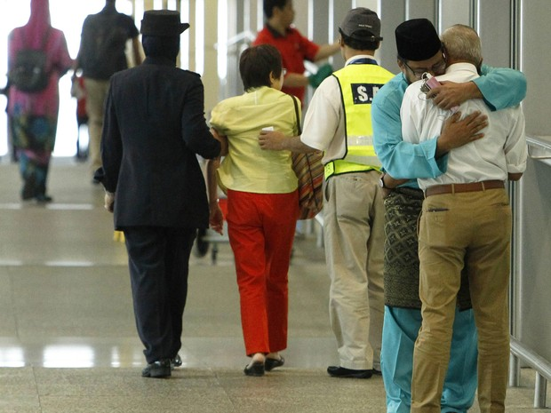 Parentes de vítimas da queda do voo MH17 se consolam com abraço no aeroporto internacional de Kuala Lumpur nesta sexta-feira (18). Local era destino do avião que caiu no leste da Ucrânia (Foto: Edgar Su/Reuters)