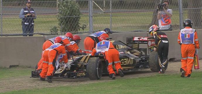 Após falha mecânica, Romain Grosjean ajuda fiscais a retirar Lotus da pista (Foto: Divulgação)