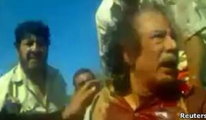 Imagem tirada de vídeo amador mostra o ex-ditador líbio Muammar Kadhafi, ferido, logo após sua captura (Foto: Reuters)