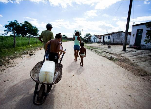 Em Olho d'Água das Flores, busca por água é diária. A moradora Creuza e os filhos voltaram de mãos vazias da torneira coletiva. (Foto: Jonathan Lins/G1 AL)