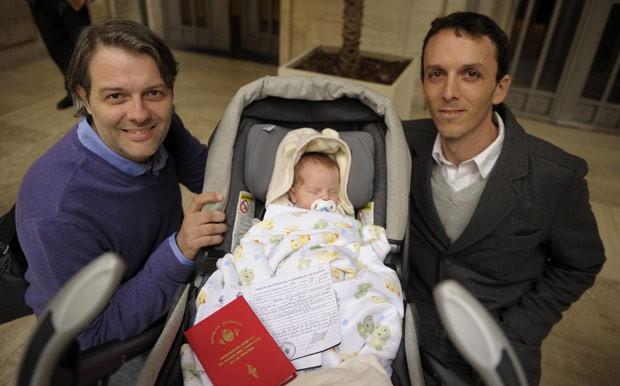 O bebê Tobias Grinblat Dermgerd ao lado de seus pais Alejandro Grinblat (à esquerda) e Gustavo Dermgerd após ter sido registrado nesta terça-feira (31) em Buenos Aires (Foto: AFP)