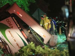 ônibus é visto ainda capotado à beira da pista após acidente na Rodovia Mogi-Bertioga, no limite entre as cidades de Mogi das Cruzes e Bertioga (Foto: José Patrício/Estadão Conteúdo)