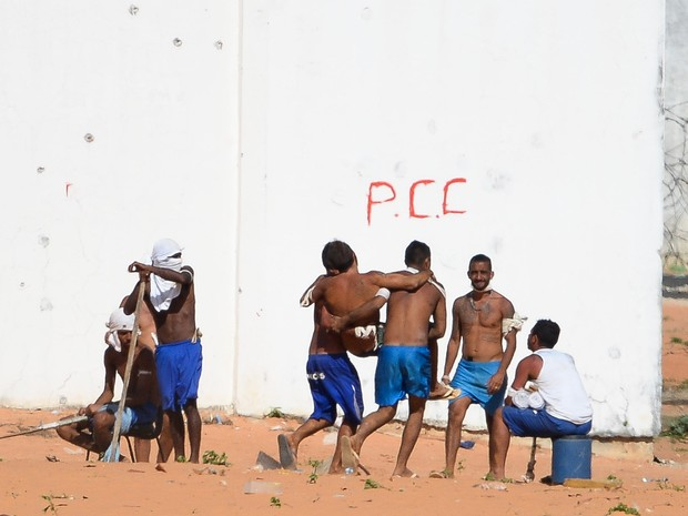 Presos carregam um detento ferido na penitenciária de Alcaçuz, no Rio Grande do Norte (Foto: Andressa Anholete/AFP)