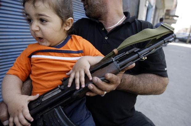 Criança é vista no colo do pai durante confrontos em Trípoli, justamente na Rua Síria (Foto: Joseph Eid/AFP)