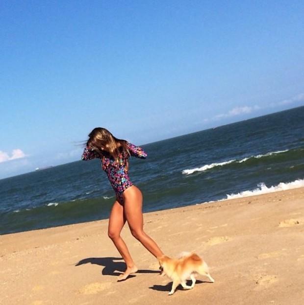 Adriana brinca com cadelinha na areia (Foto: Reprodução_Instagram)