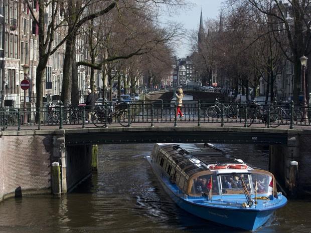 Barco passa por um dos canais de Amsterdã (Foto: Peter Dejong/AP Photo)