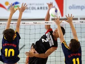 Jogador da Escola E. Dathan Cervo (SP), de preto, tenta passar pelo bloqueio do time da Escola E. Reynaldo Massi (MS), de azul, pelas Olimpíadas Escolares (Foto: Wagner Carmo / COB)