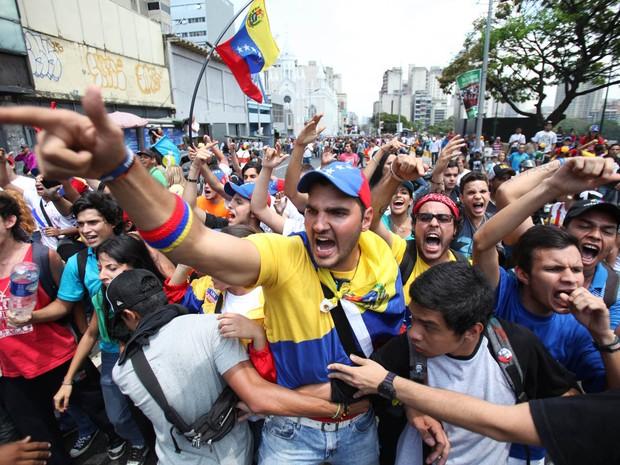 Estudantes da oposição gritam palavras de ordem contra partidários do falecido presidente venezuelano Hugo Chávez durante um protesto próximo da comissão eleitoral em Caracas, Venezuela.  (Foto: Fernando Llano/AP)
