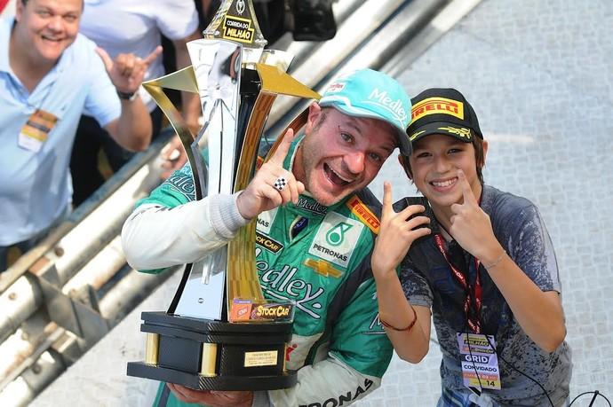 Rubens Barrichello com o filho e troféu da Corrida do Milhão (Foto: Duda Bairros Fotografia Ltda)