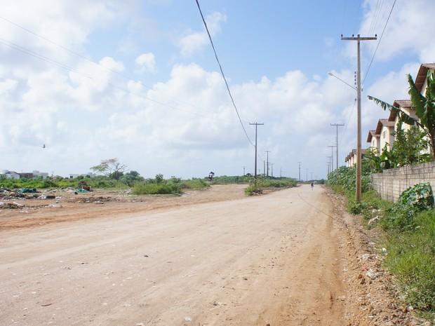 Rua que dá acesso aos residenciais é deserta, sem iluminação, com muita poeira e buracos na via (Foto: Paula Nunes/G1)