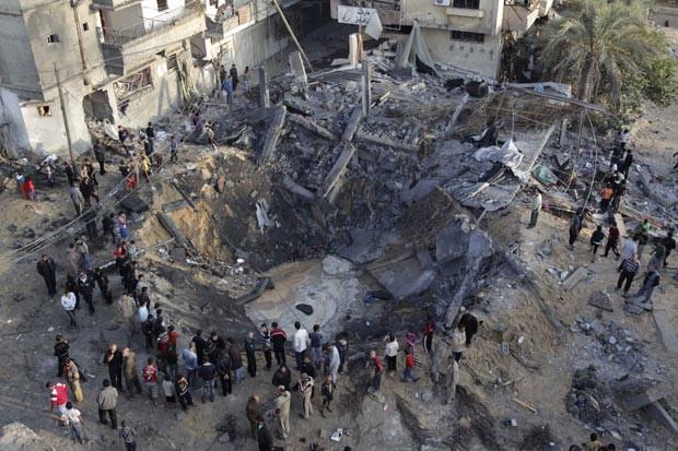 Moradores observam nesta segunda-feira (19) casa destruída por bombardeio israelense em Khan Younis, na Faixa de Gaza  (Foto: AFP)