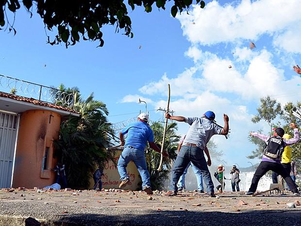 Estudantes e professores atacam a casa do governador interino com pedras nesta quarta-feira (29) (Foto: Alejandrino Gonzalez/AP Photo)