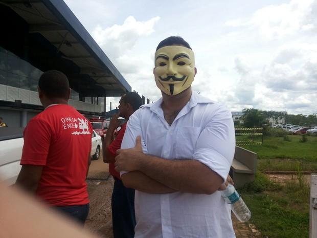 Marcel Oliveira, de 26 anos, protesta em frente ao aeroporto de Rio Branco, durante chegada de Dilma  (Foto: Janine Brasil/G1)