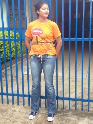 Professora de português, Maria Evilma Moreira se acorrentou ao portão do colégio onde trabalha (Foto: Vanessa Navarro/RPC)