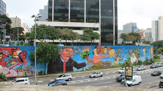 Um longo e multicolorido grafite feito em conjunto por Nina Pandolfo, Nunca e Osgemeos (Foto: Charles Humpreys/BBC)