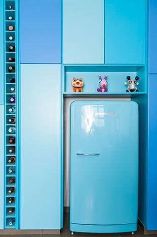 A cor da geladeira retrô, da Adélia Works, serviu de referência na escolha dos tons de azul para a pintura do armário, com as tintas esmalte acetinado (códs. 6780, 6779 e 6781), da Sherwin- Williams. Nichos na vertical guardam garrafas de bebidas (Foto: Edu Castello/Casa e Jardim)