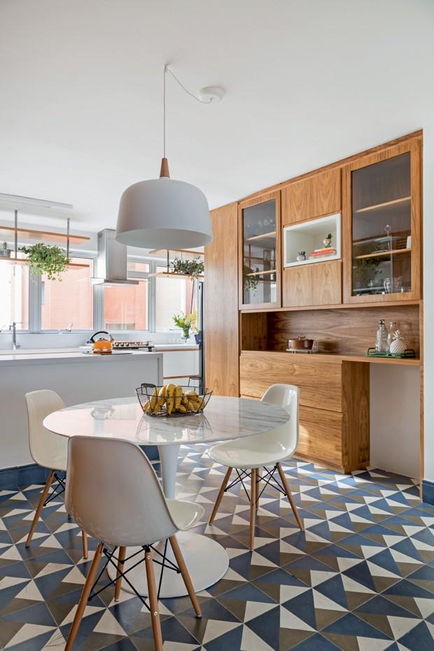 Sala de almoço. Aberta à cozinha, tem mesa Tulipe, de Eero Saarinen, da Tok & Stok, com cadeiras da Coqueluche Casa, sobre o piso de ladrilho da Dalle Piagge. Acima, luminária pendente da Lustres Yamamura (Foto: Julia Ribeiro / Divulgação)