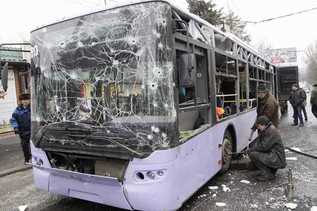 Pessoas cercam ônibus que foi atingido por morteiro em Donetsk nesta quinta-feira (22), deixando mortos (Foto: Alexander Ermochenko/Reuters)