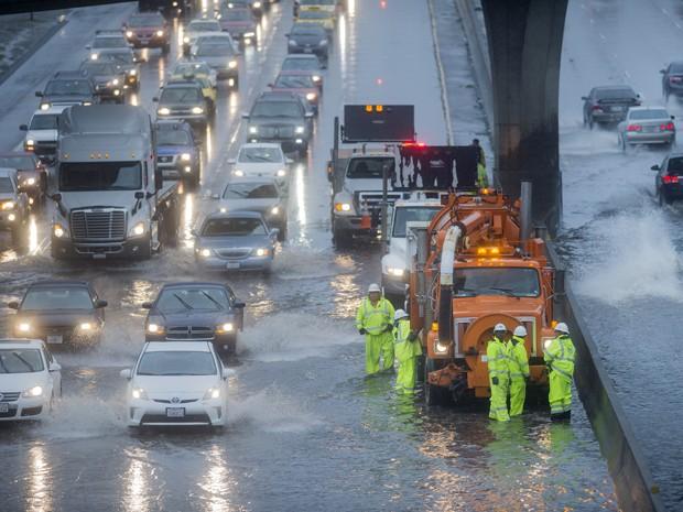 Equipe de segurança tenta desobstruir um trecho alagado da Highway 101, em San Francisco, na Califórnia (Foto: AP Photo/Noah Berger)