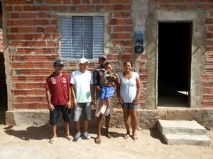 Cabeleireiro (de branco) com a família beneficiada durante a entrega das casas (Foto: Arquivo Pessoal)